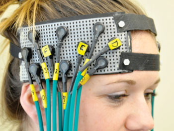 Image: Participant fitted with fNIRS headgear (Photo courtesy of University of Pittsburgh Schools of the Health Sciences).