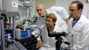 Image: From left, Guy Genin, PhD, John Boyle and Stavros Thomopoulos, PhD, watch as a sample is exposed to stress and force. They have developed algorithms that may lead to the ability to identify weak spots in tendons, muscles and bones (Photo courtesy of Washington University in St. Louis).