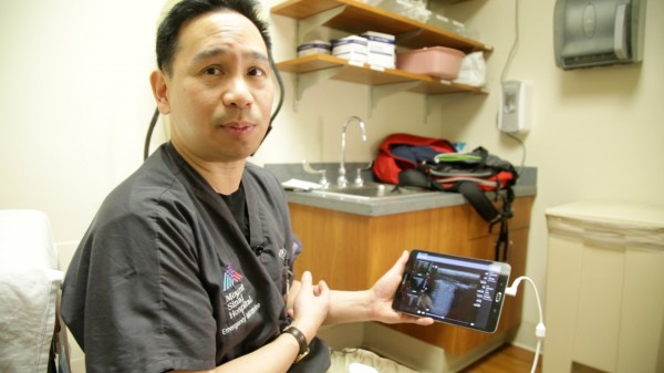 Image: Dr. James Tsung, MD, showcases a lung ultrasound display on a tablet (Photo courtesy of Mount Sinai Hospital).
